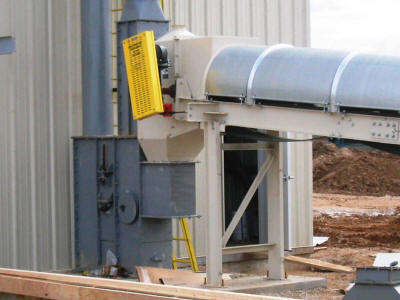 Covered troughing belt conveyor with head box enclosure transferring to the boot of a bucket elevator.